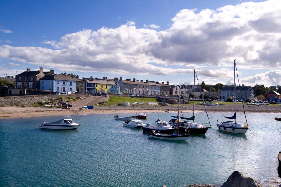 Boats on still waters at Greystones Harbour with a backdrop of colourful houses
