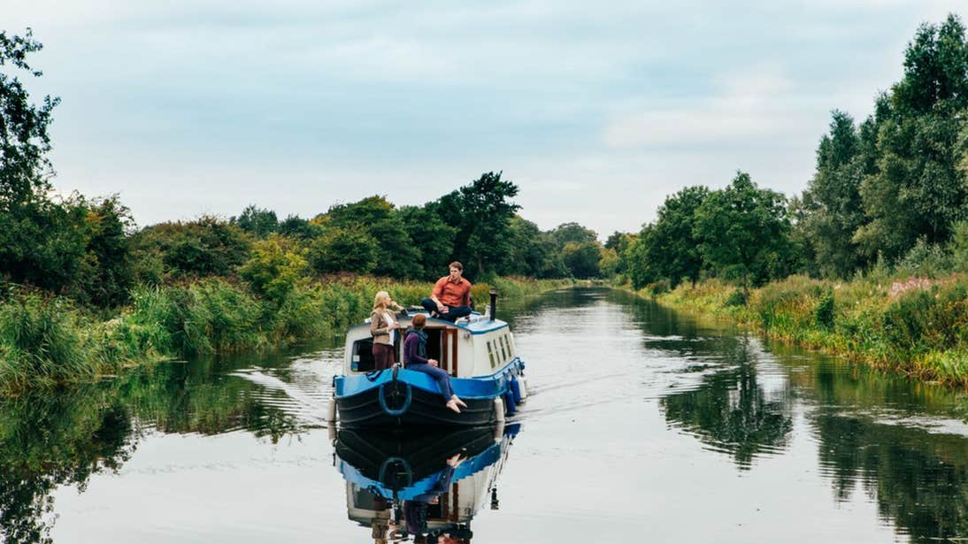 People sailing on a blue boat with Sallins Grand Canal barge trip in County Kildare