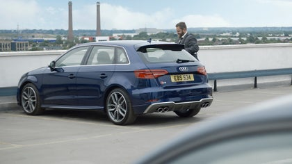 A guy next to a blue Audi S3 in a car park.