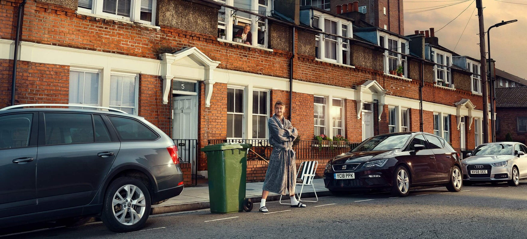 A man reserving a kerbside parking space by standing on it
