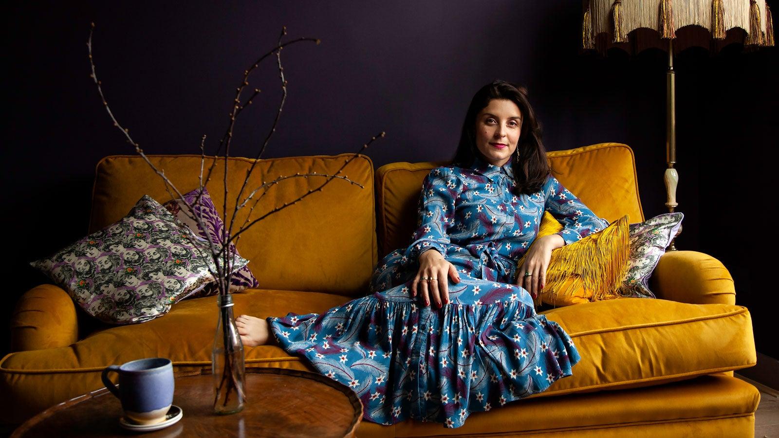 Jessie Burton sits in a blue dress on a yellow velvet sofa