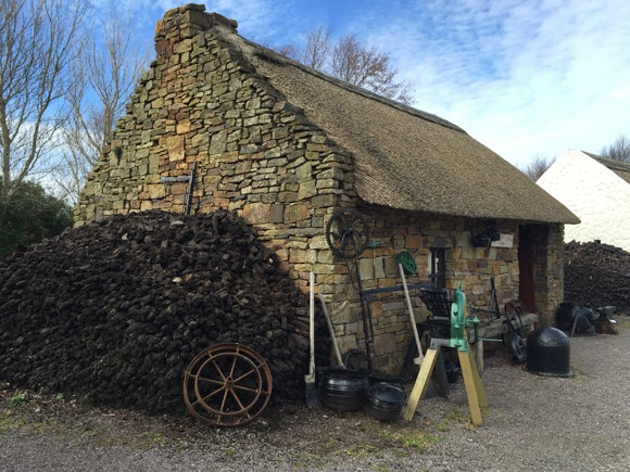A recreated blacksmith's forge: a small stone cottage with a thatched roof and tools outside on a gravel path