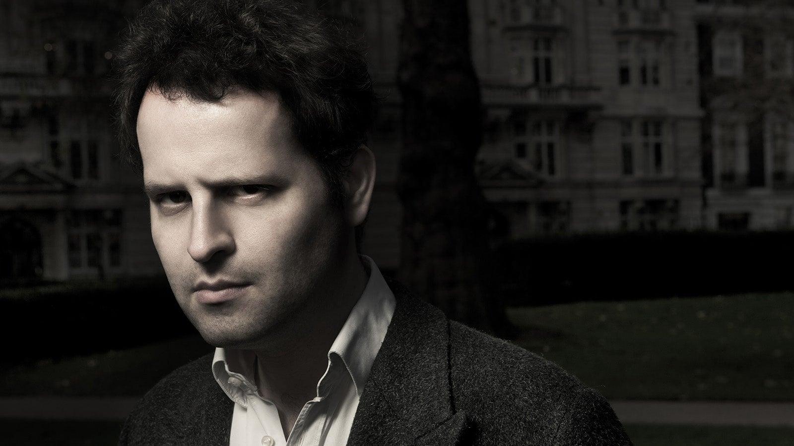 A black and white headshot of Adam Kay
