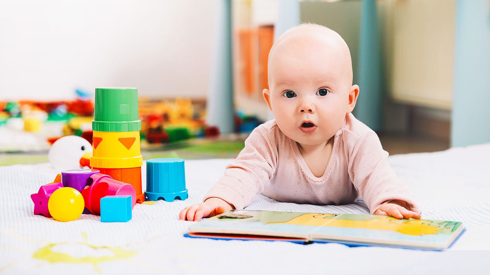 Baby led on floor with an open book and stacking toys
