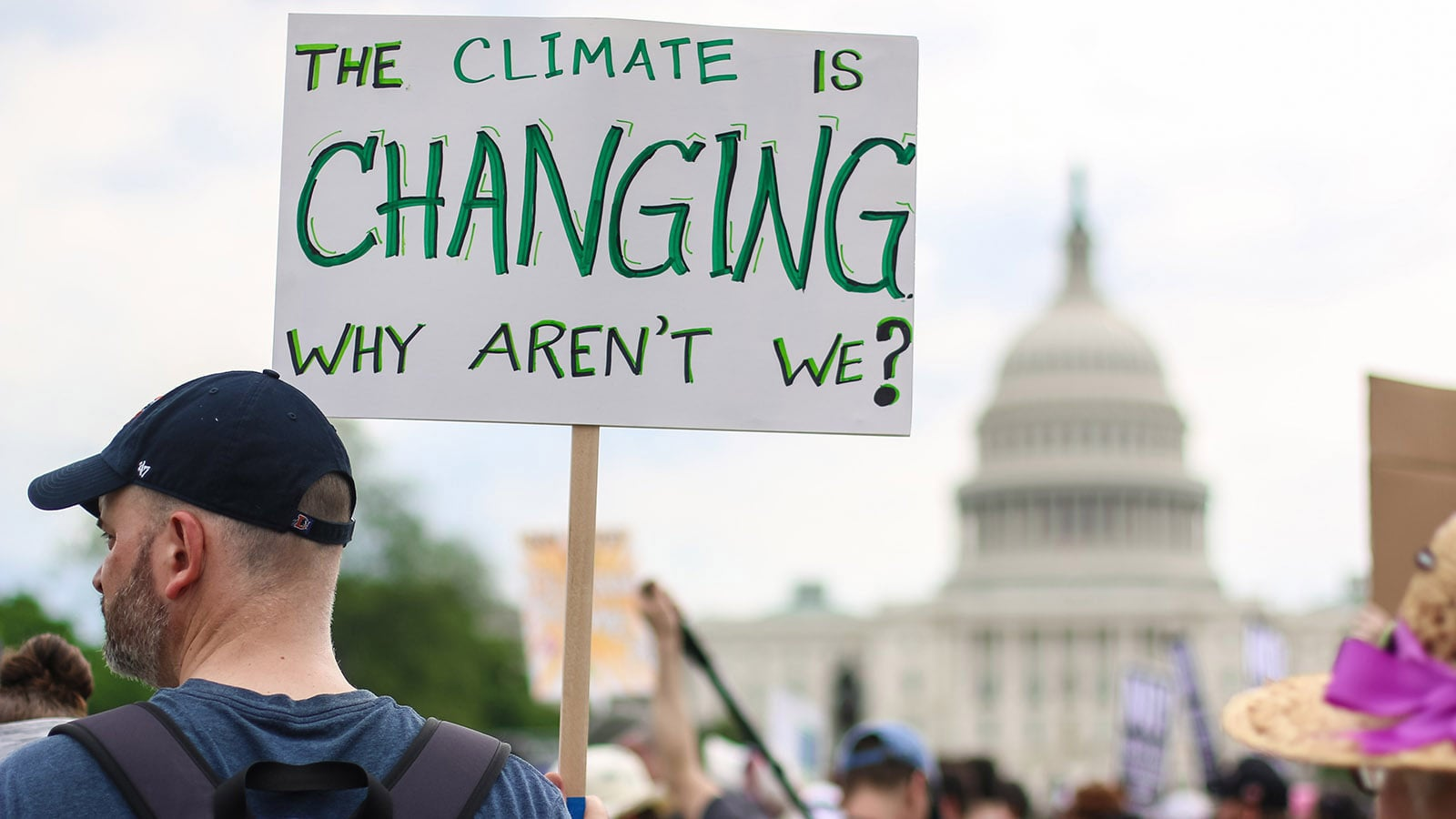 Man holding placard which says The Climate is Changing Why Aren't We?