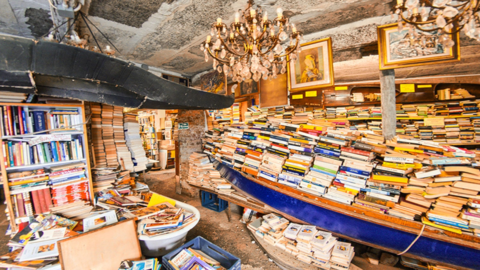 a crowded second hand bookshop wth a row-boat crammed full of books n the centre of the room