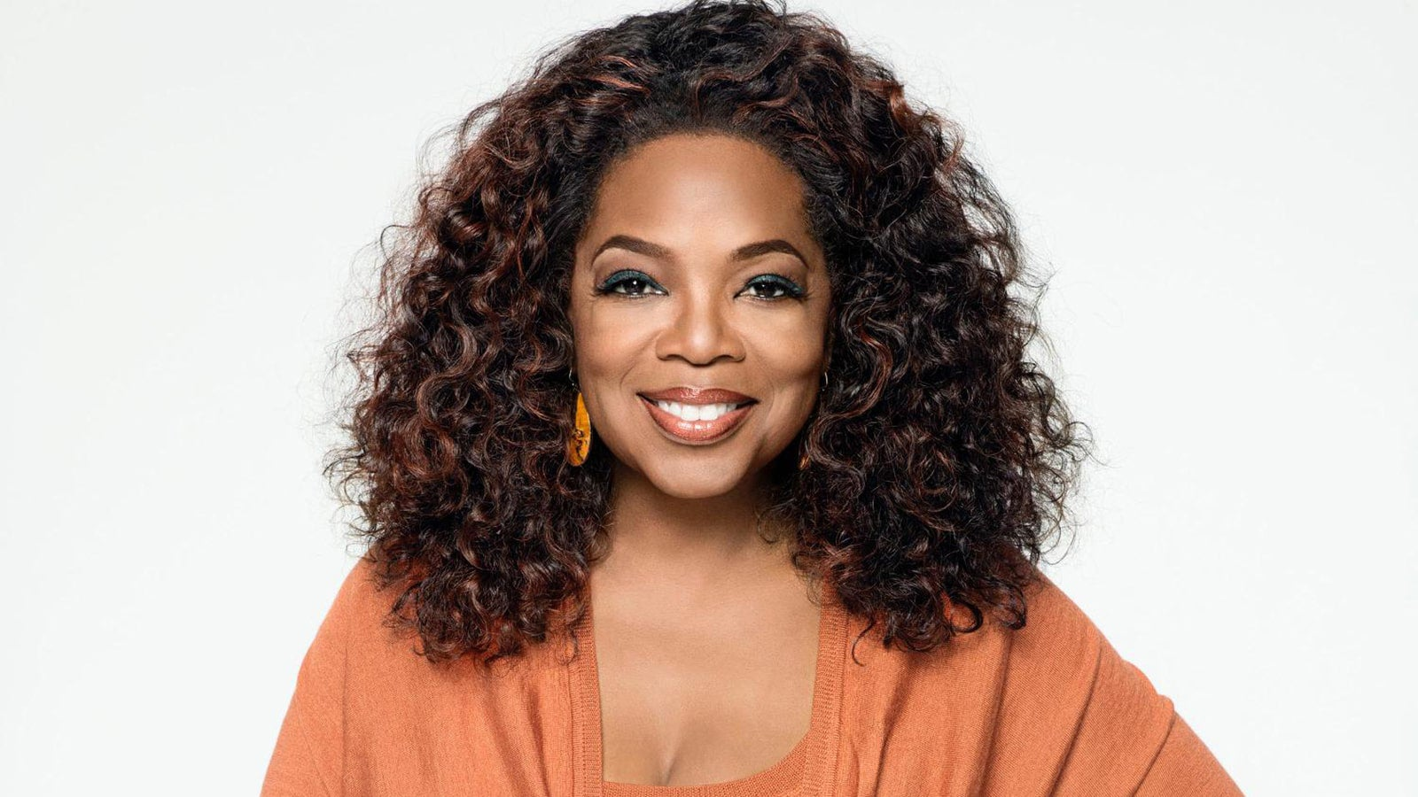 A photograph of Oprah Winfrey in an orange top against a white background.