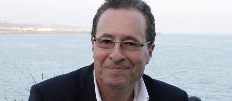 Close up photograph of Peter James in front of the ocean