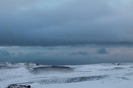 An expansive, snow covered, rocky and barren landscape with dark grey clouds rolling above