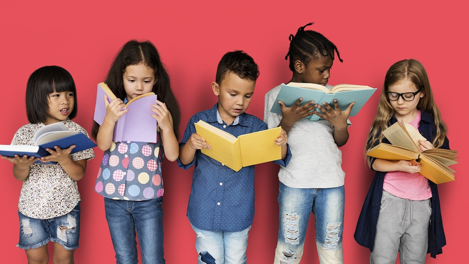 Two young girls and three young boys stood in a line against a pink wall looking at books