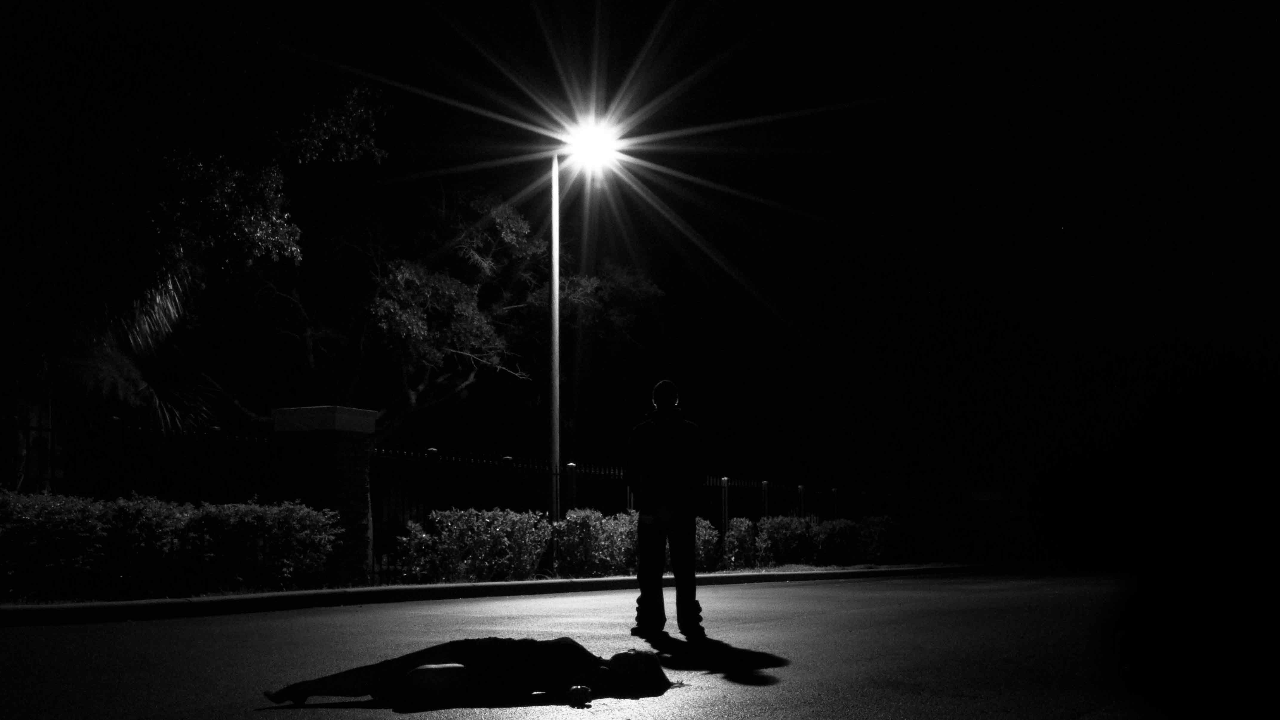 Dark figure standing beneath a street light over an unconscious figure