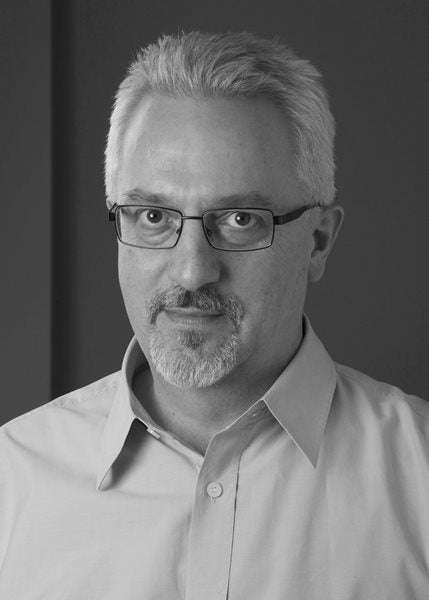A black and white photograph of author Alan Hollinghurst.