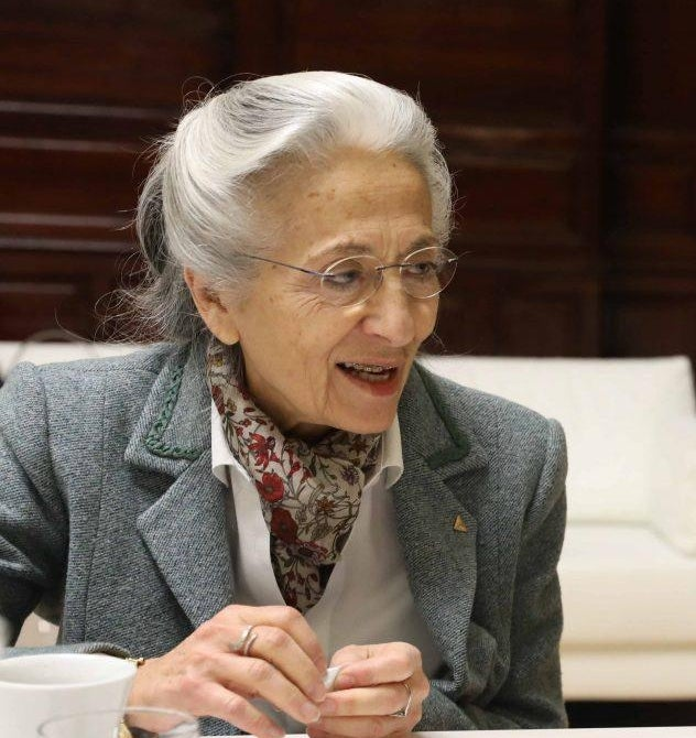 A colour photograph of Rita Levi-Montalcini mid-conversation wearing a grey suit
