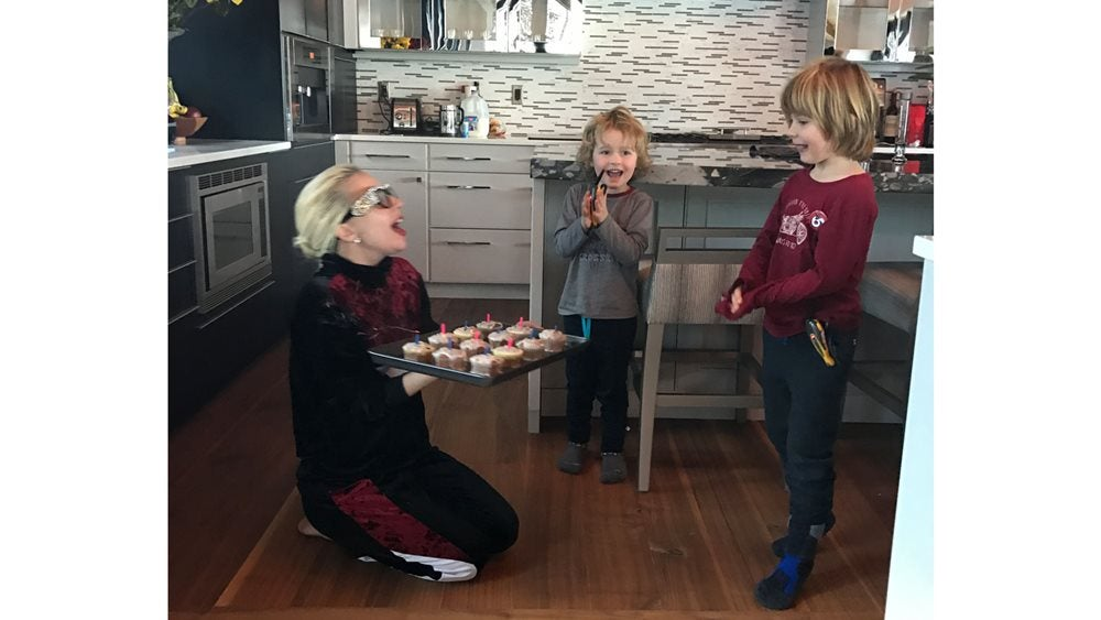 lady Gaga in the kitchen on her knees with a tray of cupcakes