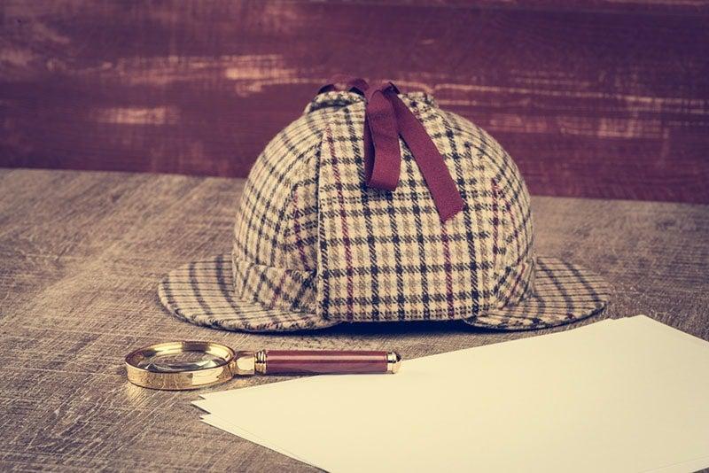 Deerstalker, Magnifying glass, paper on a wooden table