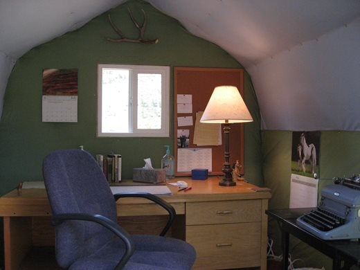 writing desk in a cosy room with a green wall, a lamp on the desk and a typewriter to the right-hand side