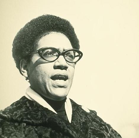 Black and white photograph of Audre Lorde mid-speech