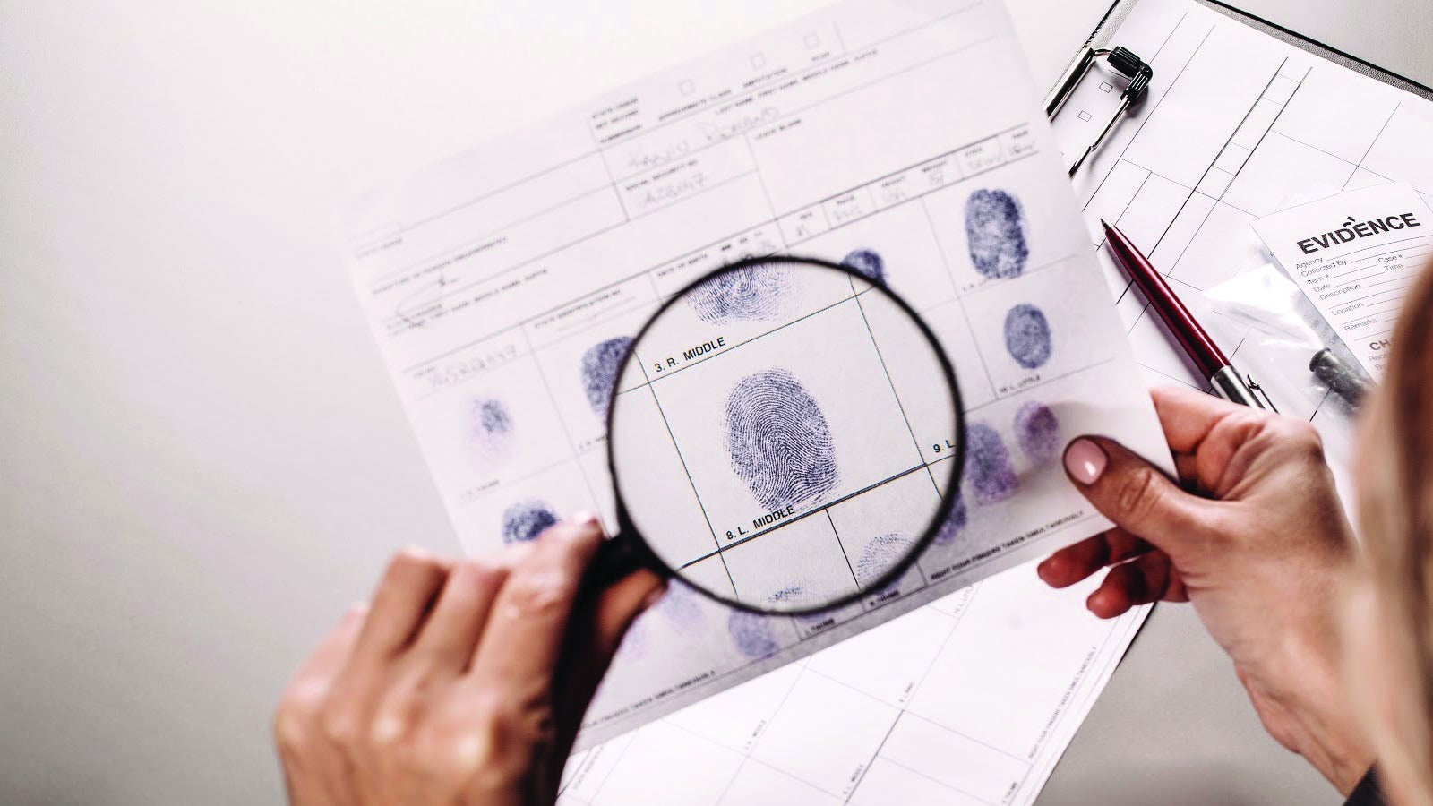 A pair of hands closely examines a set of fingerprints with a magnifying glass.