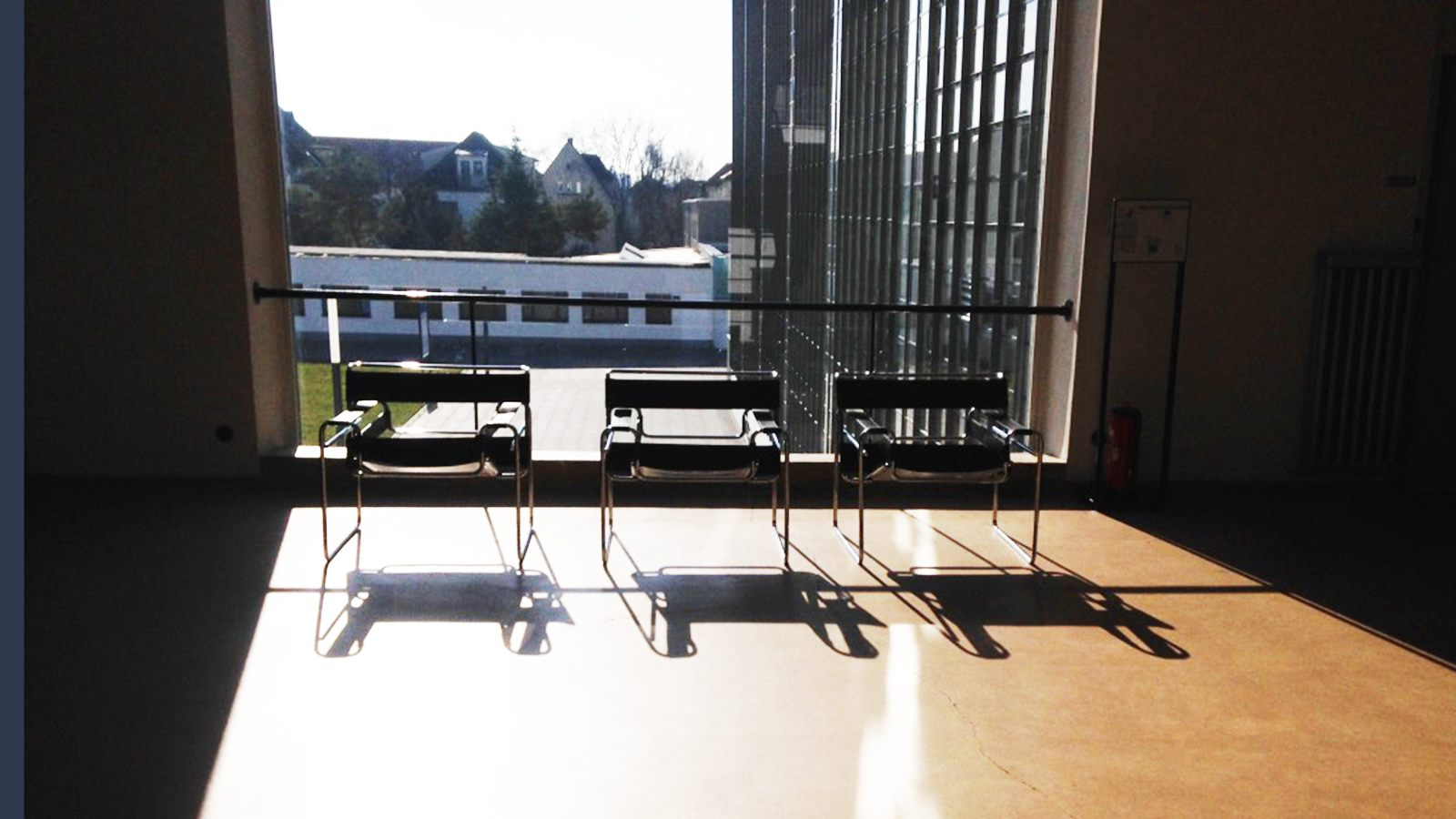 Three kandinsky chairs in front of a window, casting long shadows on the floor