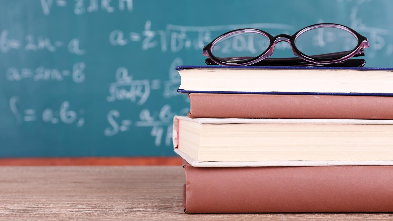 A pair of glasses on top of a stack of books, with a blurred chalkboard in the background