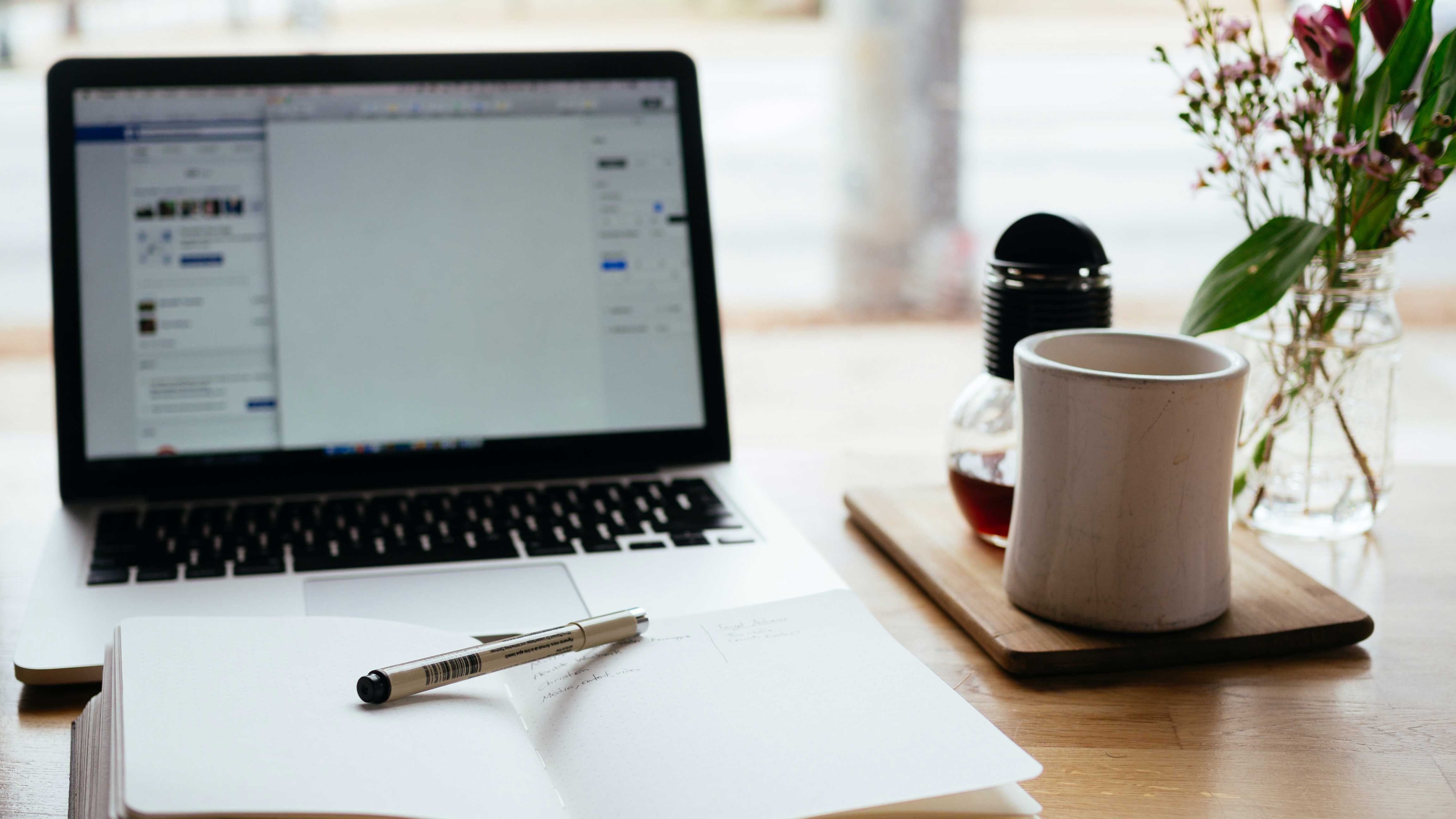 A laptop with an open notepad in front and a cup of coffee to the right