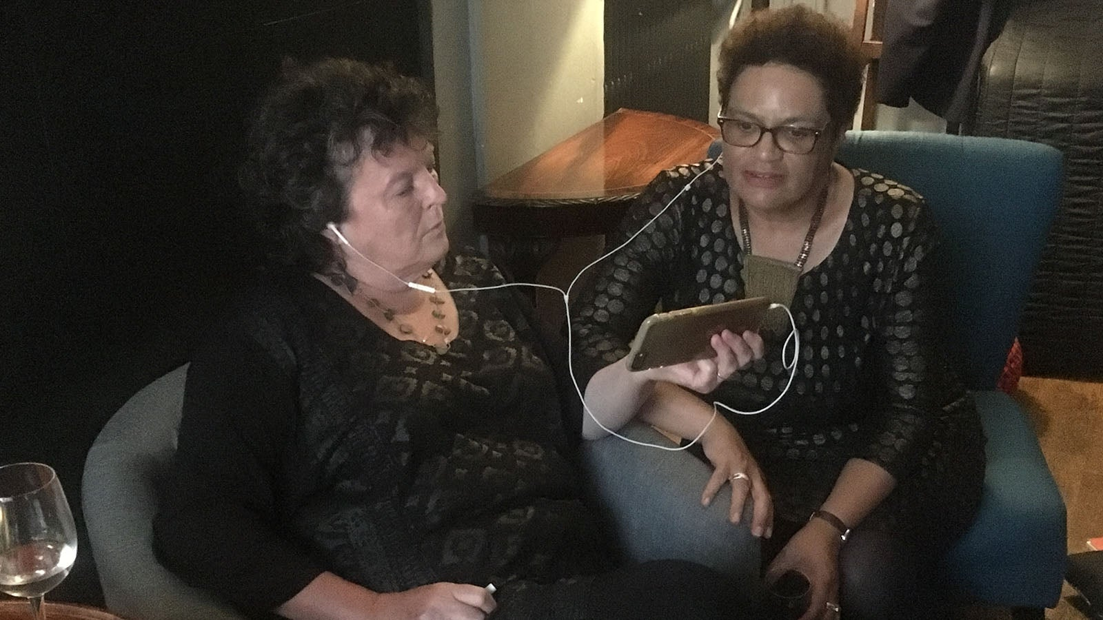 Carol Ann Duffy and Jackie Kay sharing headphones to watch the match backstage
