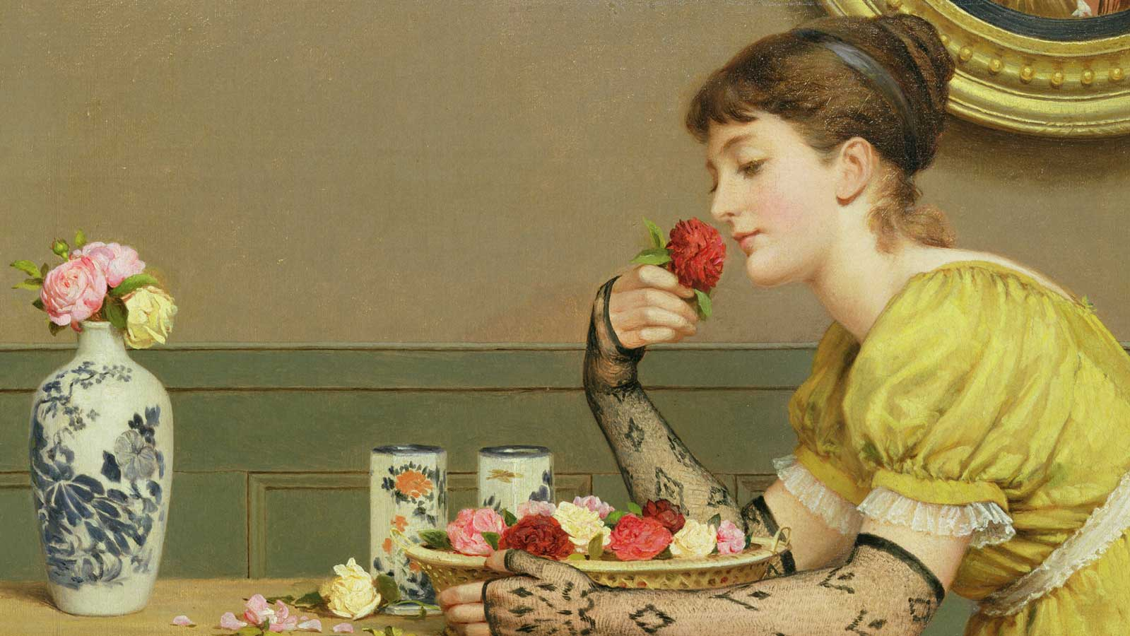 Young girl sits at a table smelling a rose - taken from the cover of Vanity Fair