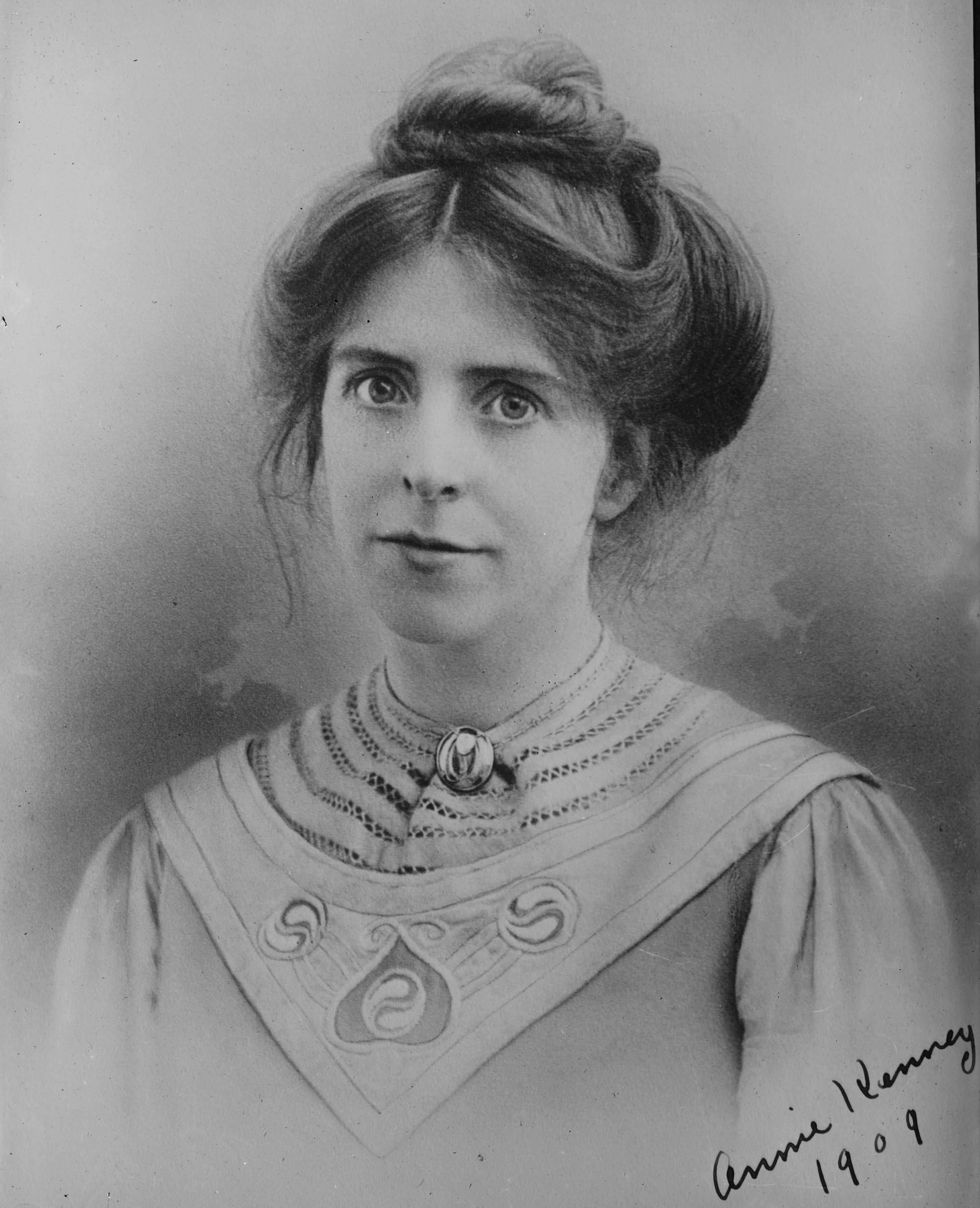 A black and white photograph of Annie Kenney smiling, taken in 1909