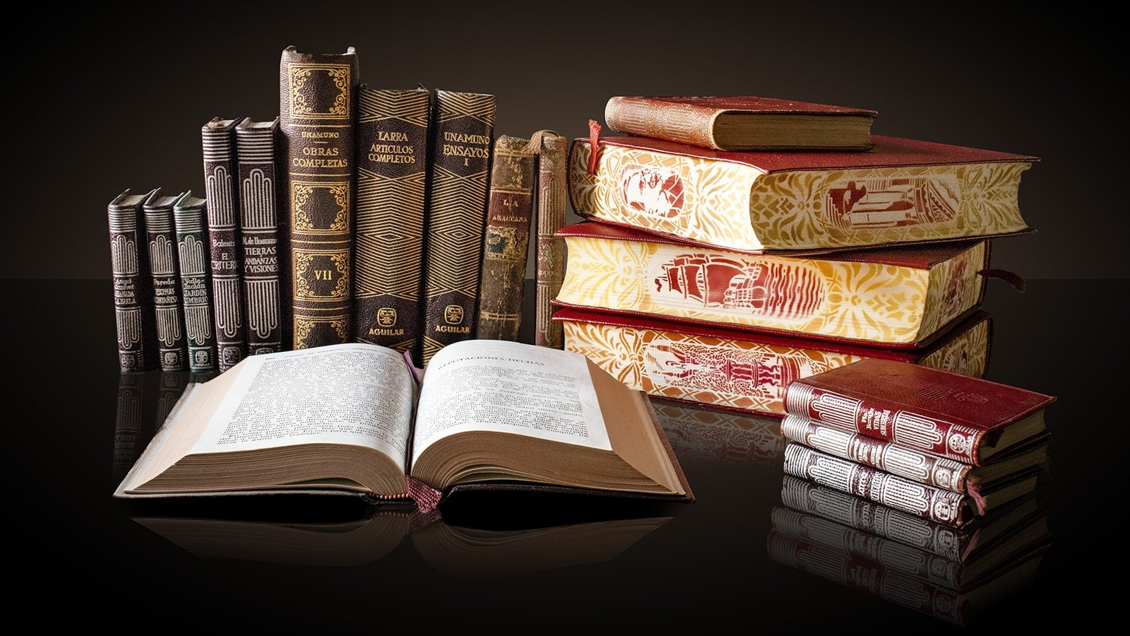 Old hardback leather bound books on a black table