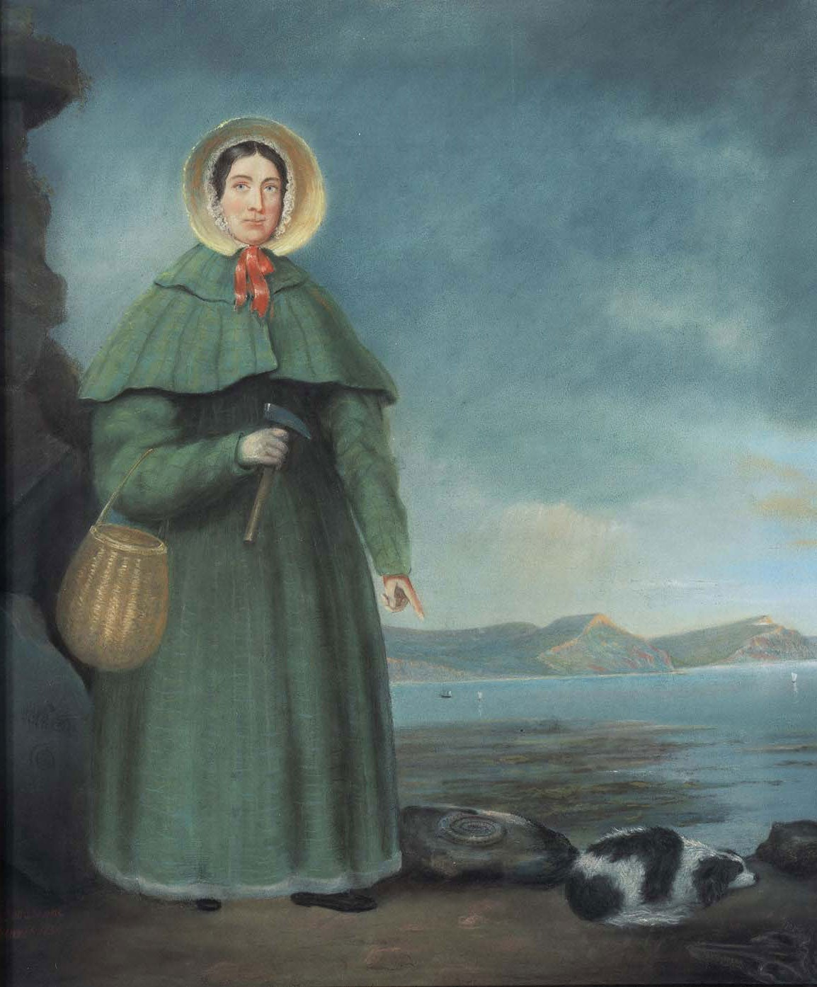 Colour painting of Mary Anning, standing on a beach, holding a small basket and hammer, pointing down to the newly discover fossil of an ammonite