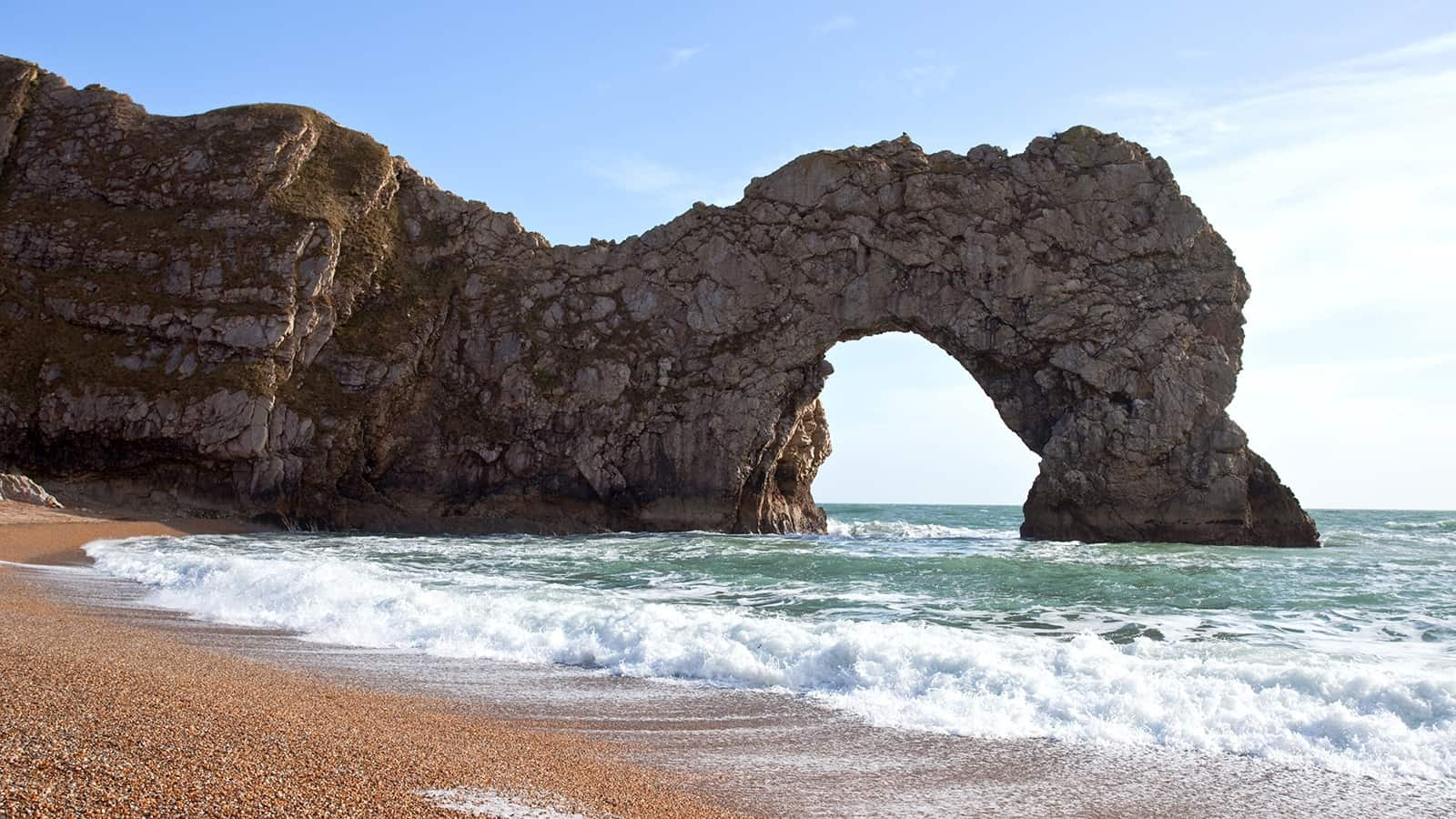 Durdle Door in Dorset with the sea beneath, on a clear summer day