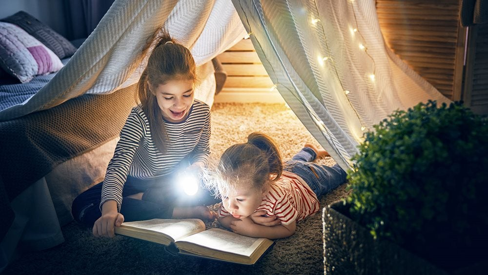 Two girls reading together in an indoor tent