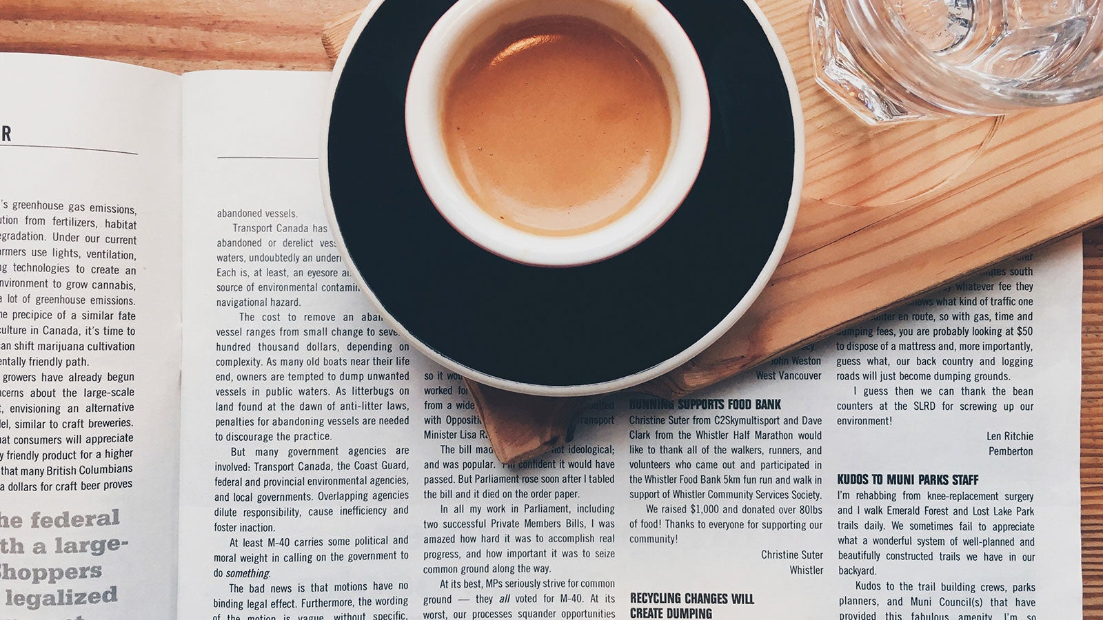 Coffee cup next to an open newspaper