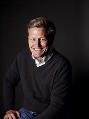 A headshot of David Baldacci in a white shirt and a black jumper