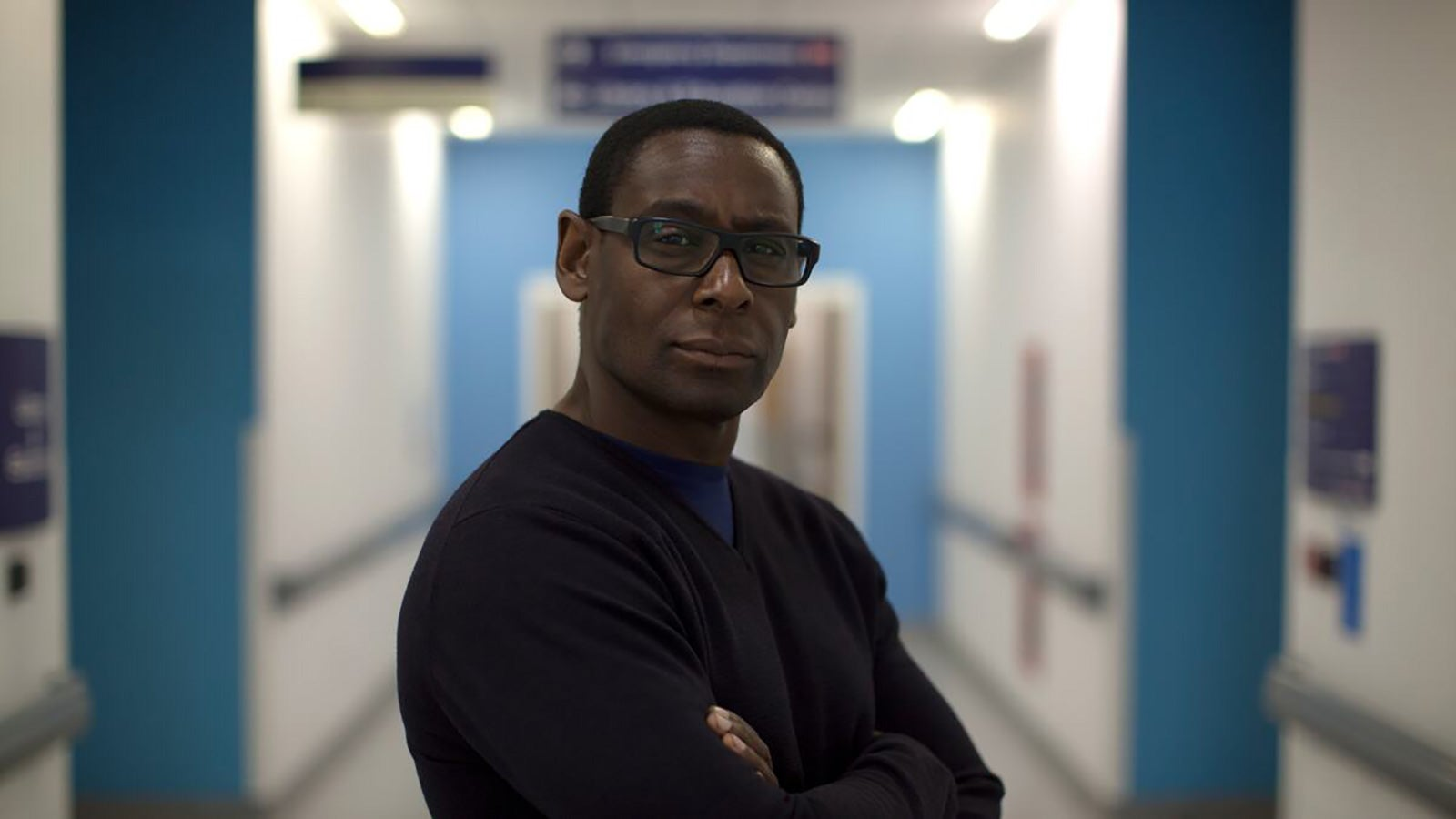 Actor David Harewood stands facing the camera with his arms crossed in a hospital ward.