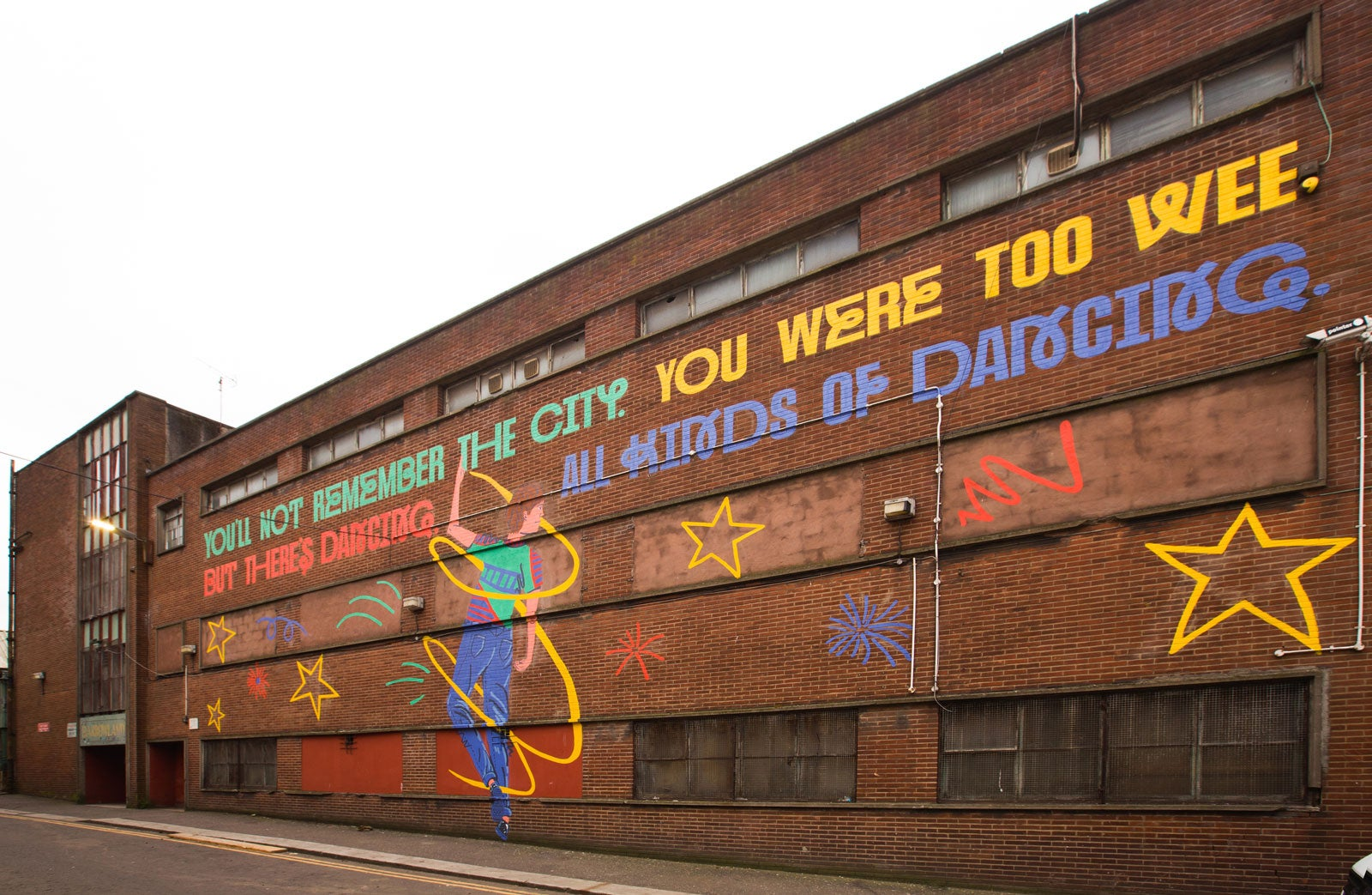 The side of Barrowland, an industrial looking red brick building, painted with a large 30m mural which shows a young boy spinning, surrounded by stars, and above it the words: 'You'll not remember the city. You were too wee. But there's dancing, all kinds of dancing'