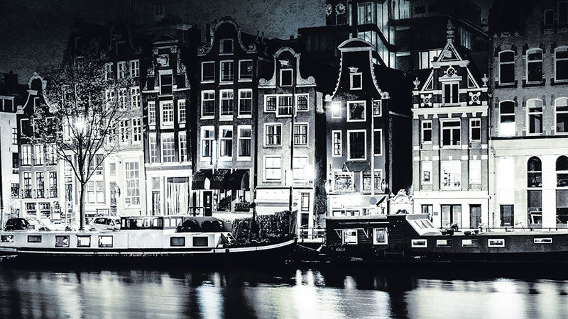 A black and white photograph of an Amsterdam street at night. Lights are on in some of the canal houses and a canal boat idles on the water.