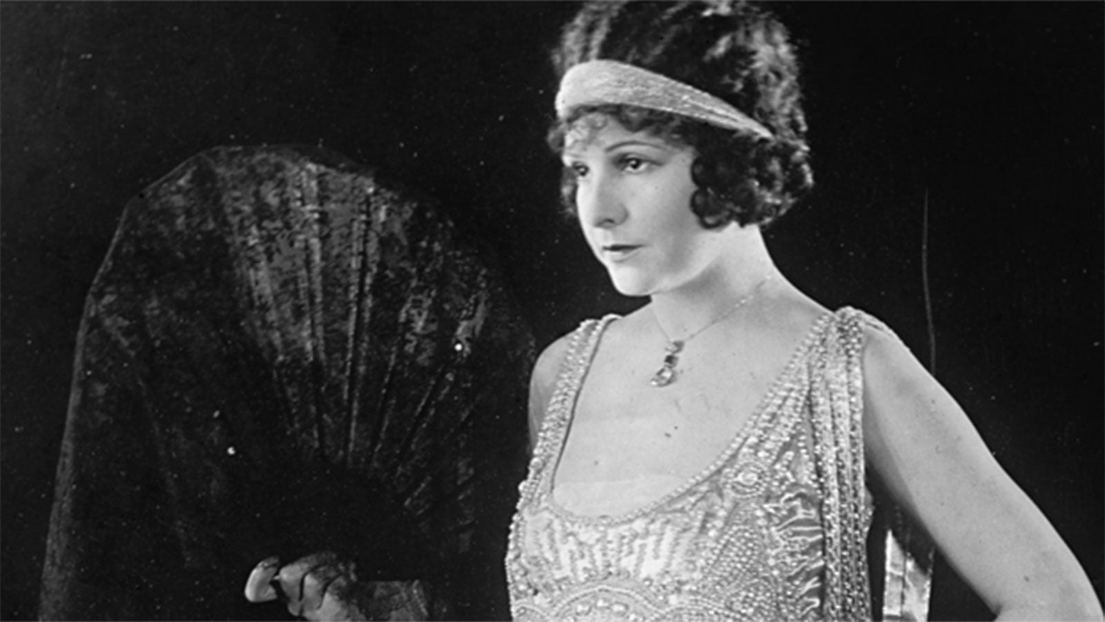 Photo of a flapper girl holding a fan