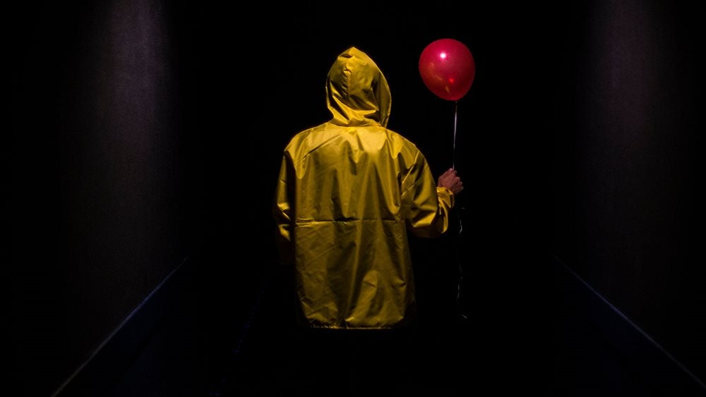 A person wearing a yellow rain jacket holding a red balloon