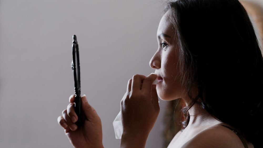 Woman looking in mirror holding tissue