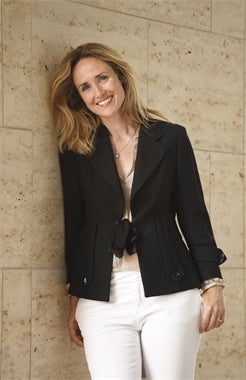 Author Karen Swan in white trousers and a black jacket leaning against a wall smiling