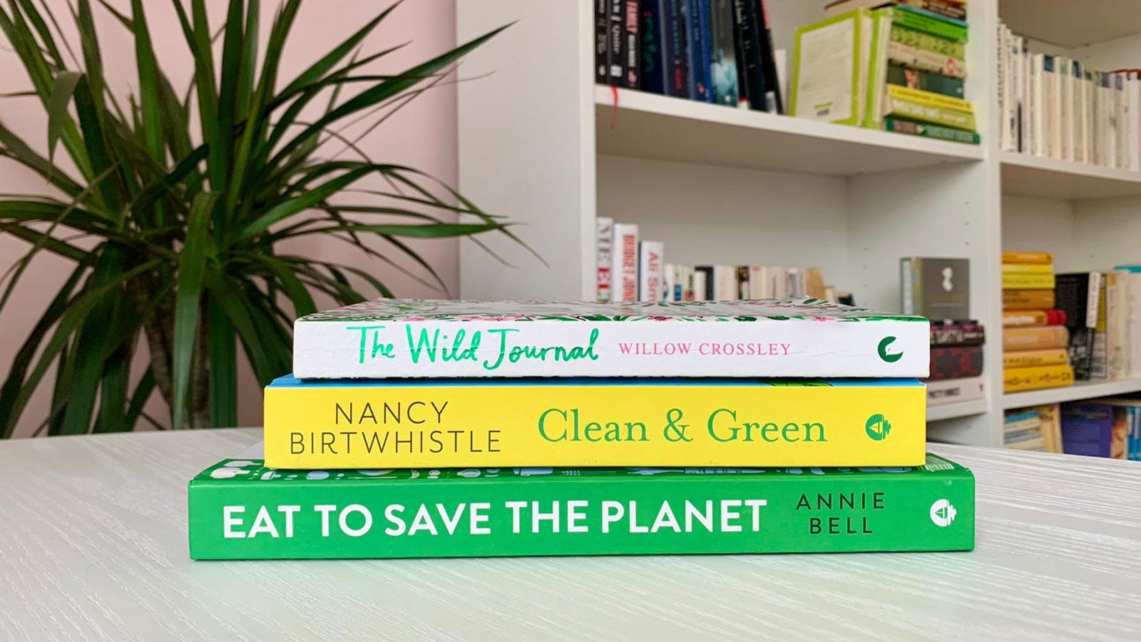 Eat to Save the Planet, Clean & Green, The Wild Journal stacked on a white table in front of a bookcase and a plant.