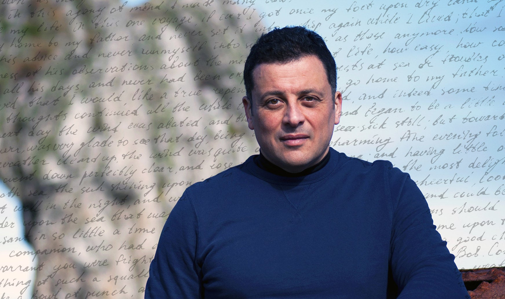 Adam Hamdy on a beach with a background of words