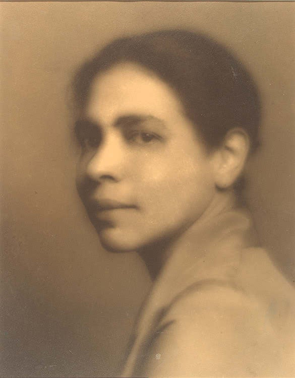 A sepia toned, close-up photograph of Nella Larsen, looking to camera with a slight smile