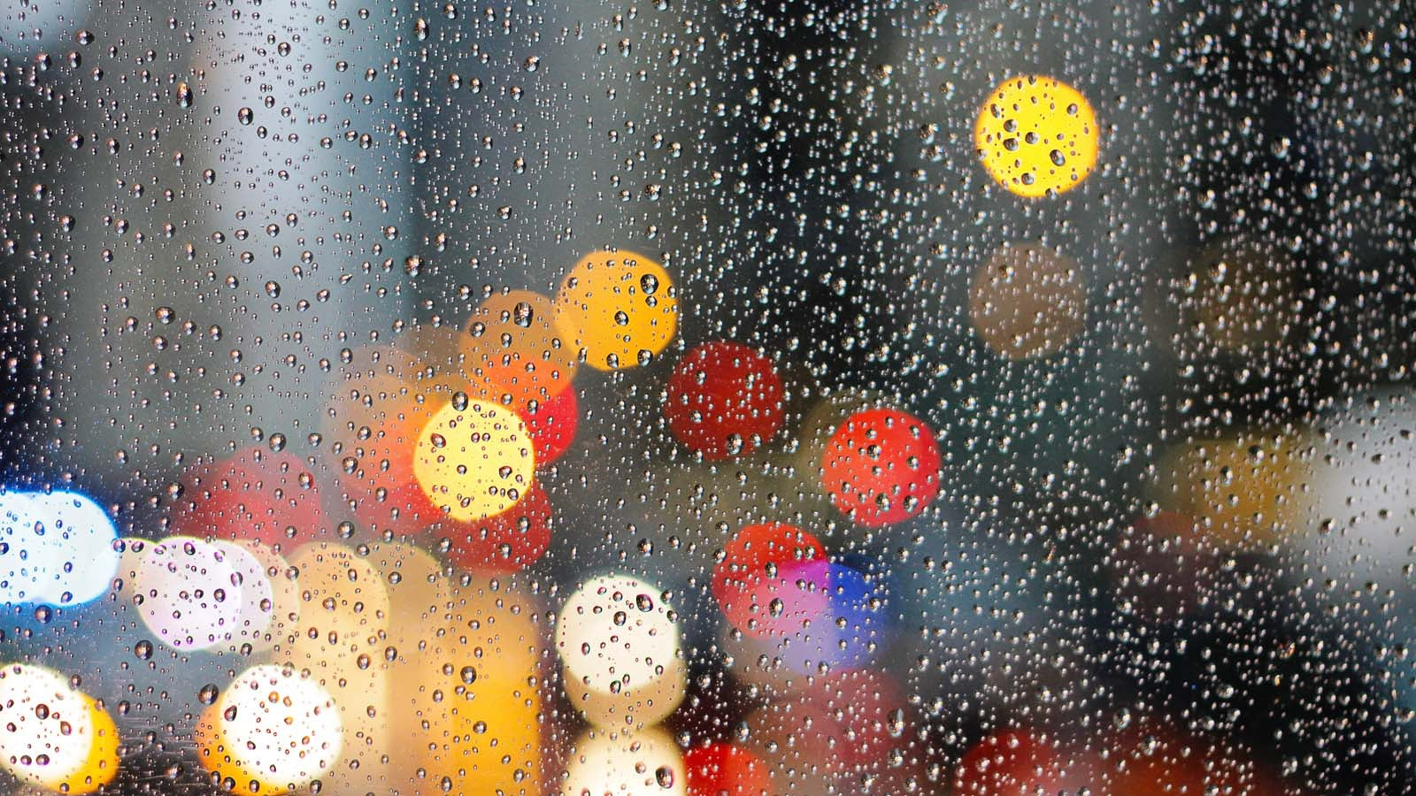 window with water droplets and blurred city lights