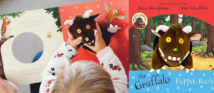 A young child playing with The Gruffalo puppet book.