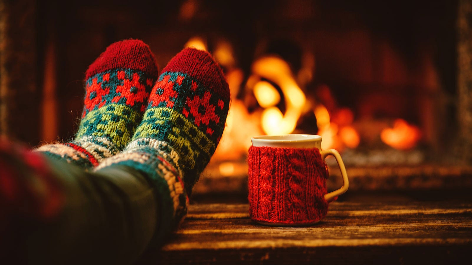 A pair of feet in warm Christmassy socks, beside a mug wrapped in cosy, both in front of a roaring fire.