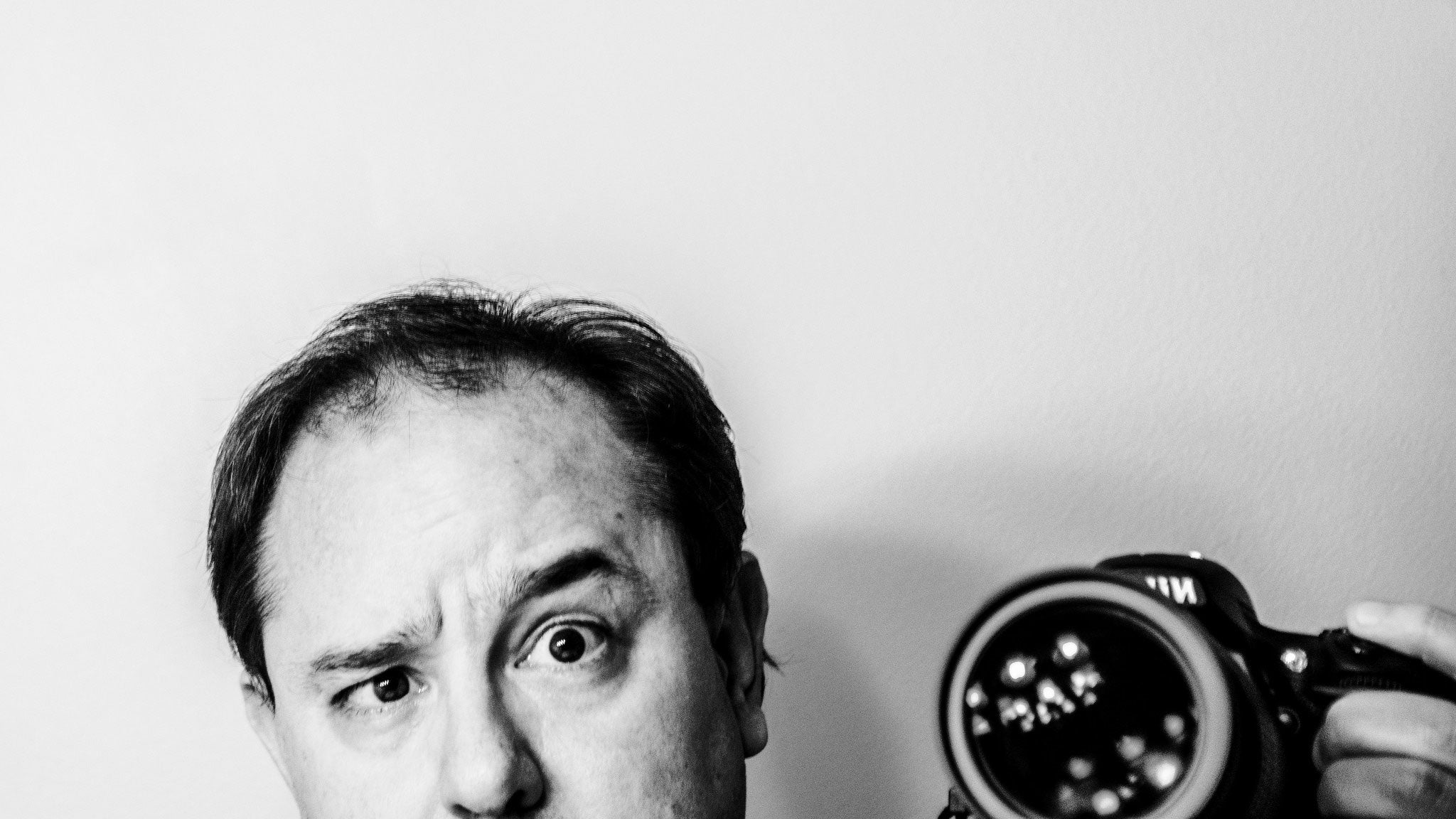 A black and white photograph of John Scalzi taking a photograph of himself, pulling a funny face