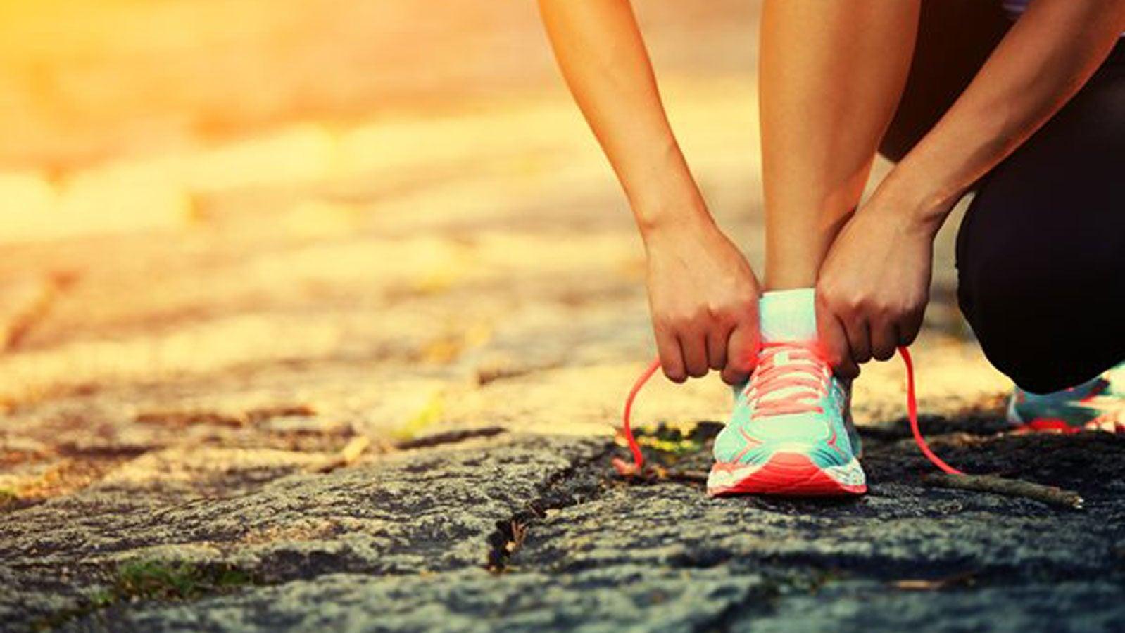 A runner bending down to tie her shoe