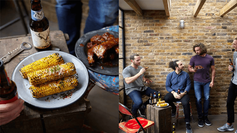 Joe Wicks with friends, corn on cobs, BBQ ribs and beer on a wooden surface